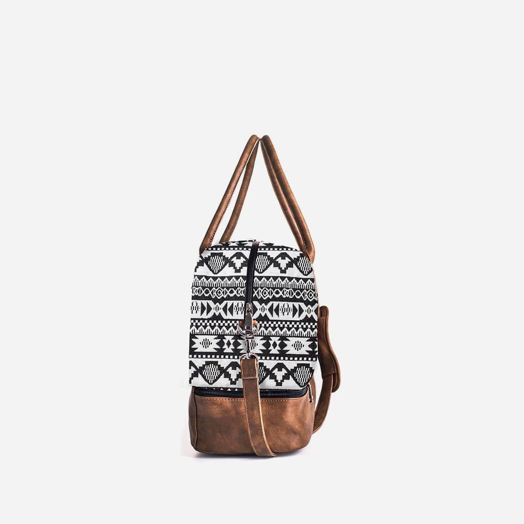 Côté du sac voyage 48h en toile avec motifs noirs et blancs et cuir marron.