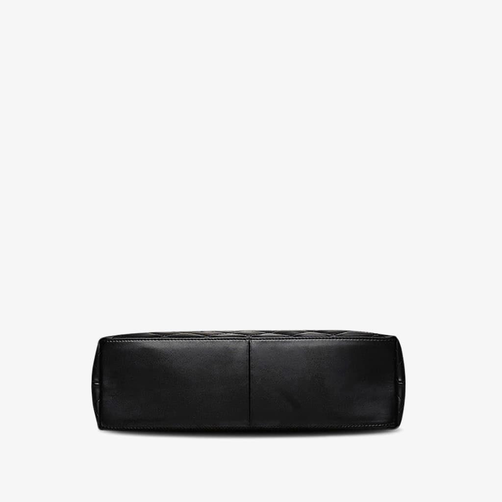 Dessous du sac à main cabas en cuir noir matelassé et à chaine.