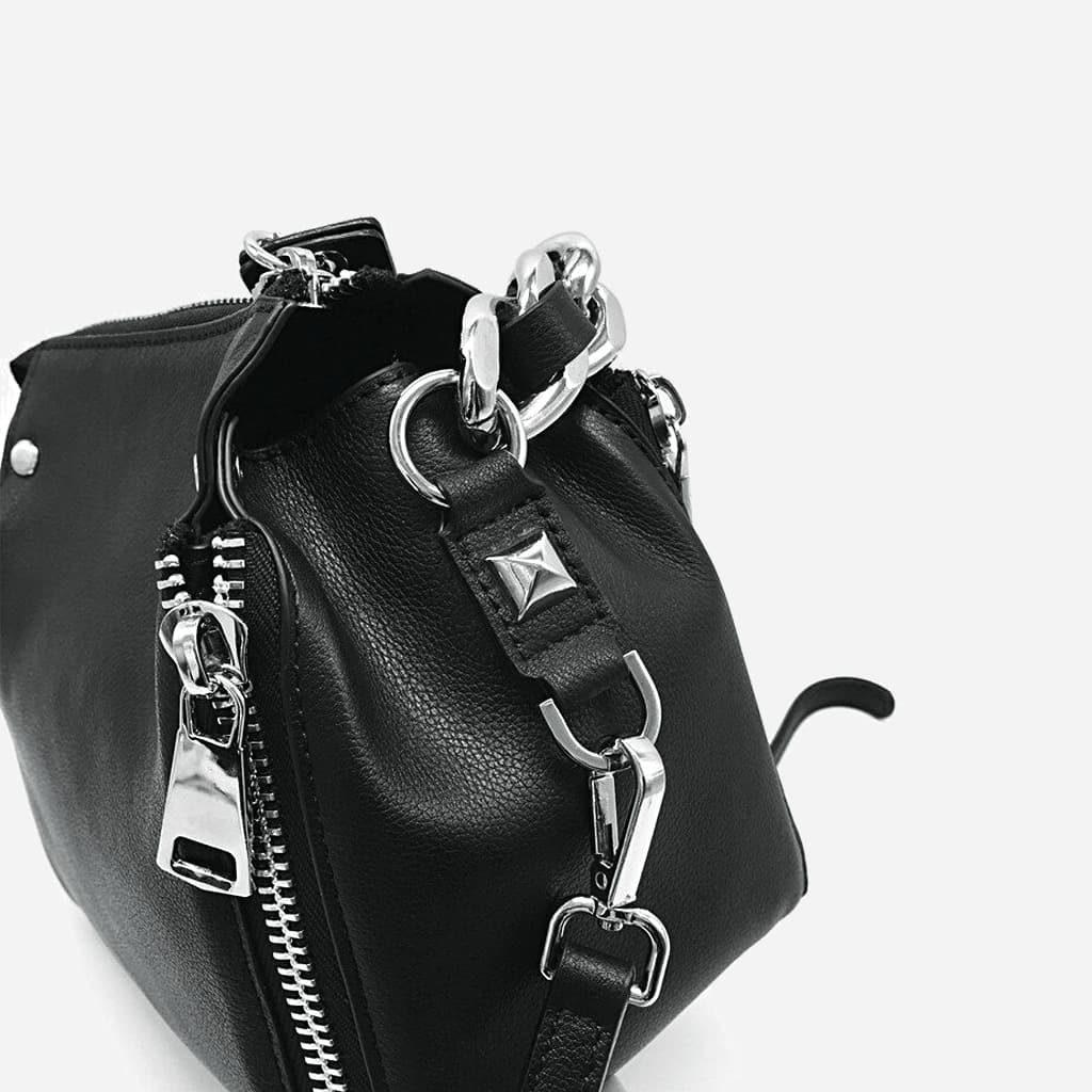 Détails encoche, mousqueton de la bandoulière et empiècement métallique argenté du sac à main à chaîne en cuir véritable noir.