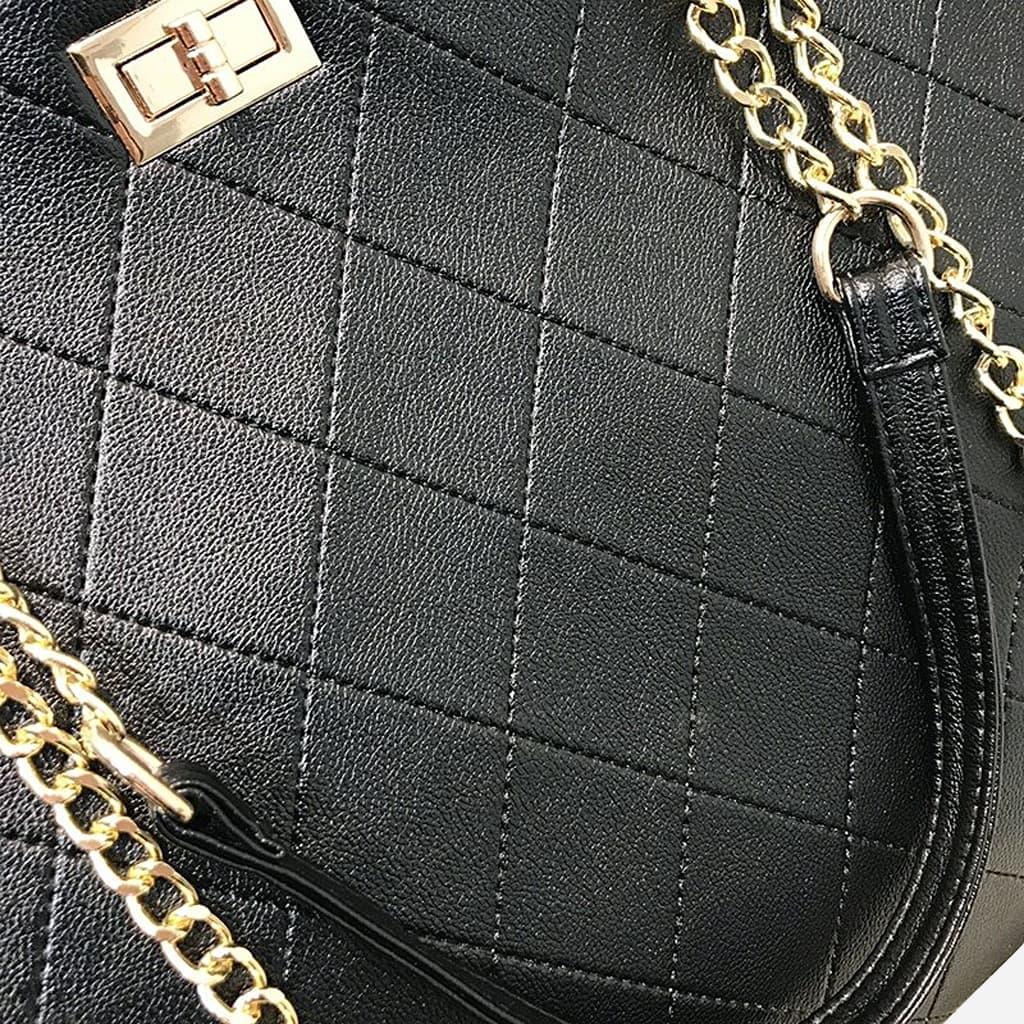 Bandoulière en cuir noir avec chaînes et moraillon dorés.