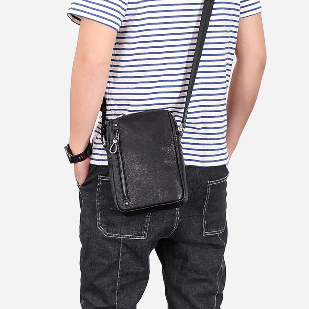 Petit sac en cuir véritable noir porté par un homme en bandoulière.