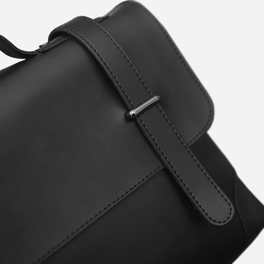 Zoom cuir, rabat, coutures et bride à boucle de la sacoche besace bandoulière en cuir noir pour homme.