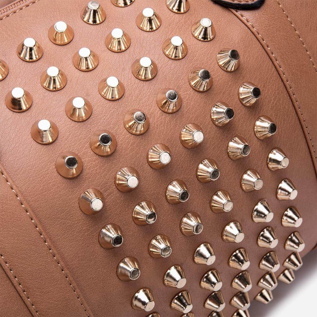 Détails des clous sur le cuir du sac à main clouté en cuir brun et beige type sac bowling.