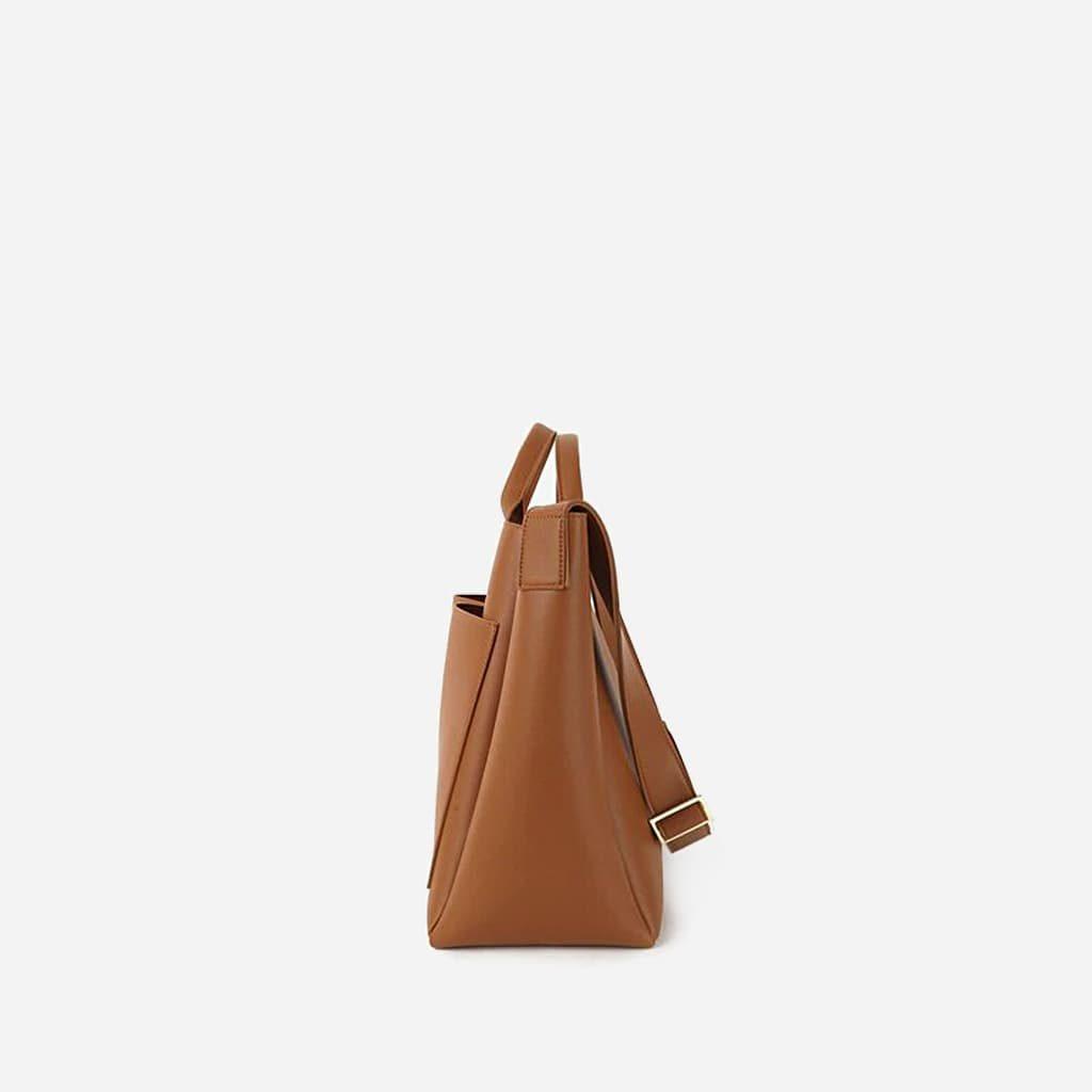 Côté du sac cabas cuir brun marron pour femme avec deux grandes poches extérieures à l'avant.