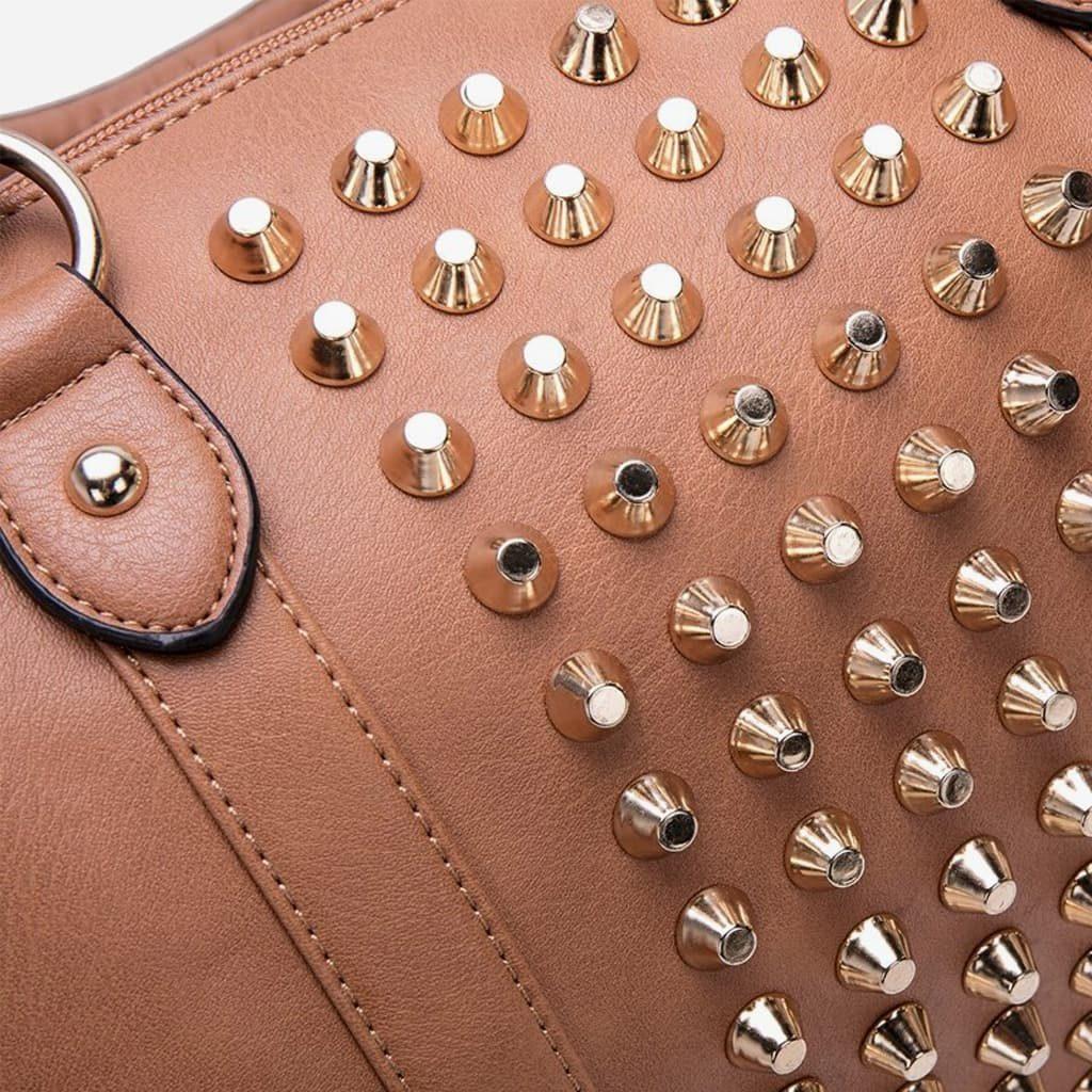 Zoom sur les clous dorés et le travail du cuir brun et beige.