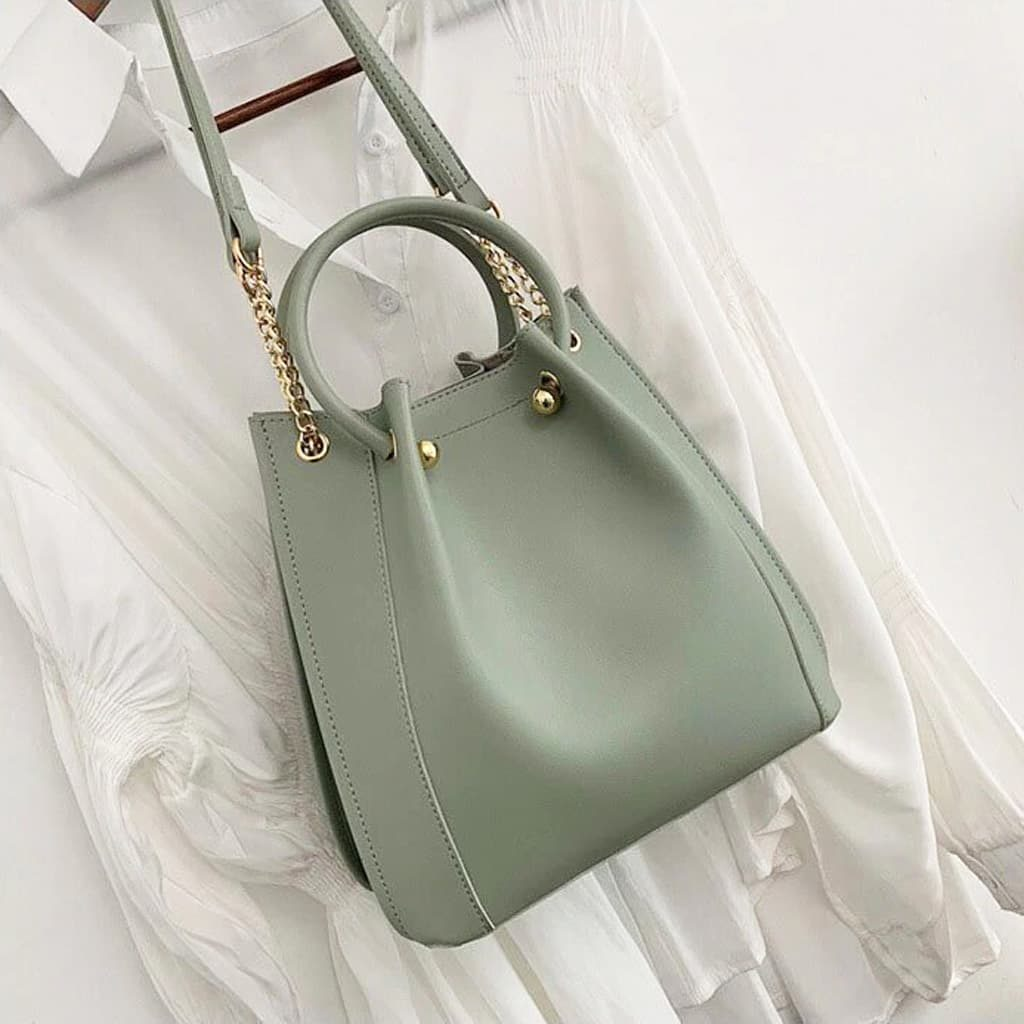 Sac fourre tout cuir vert façon sac seau avec pliures, bandoulière à chaîne et dorure.