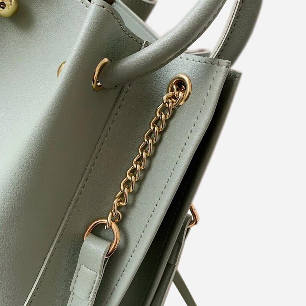 Zoom sur les maillons de la bandoulière à chaîne dorée, les anses et les oeillets dorés.
