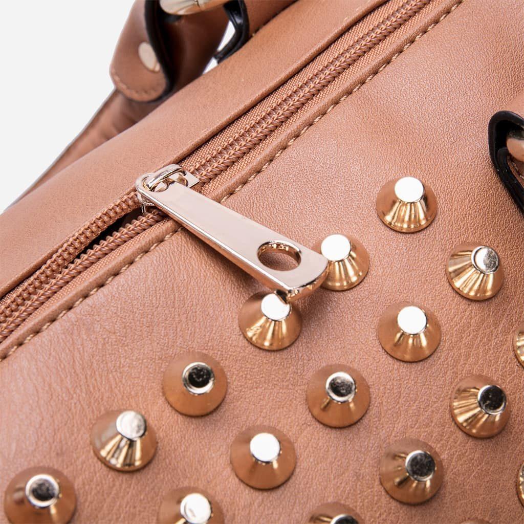Zoom sur le zip doré, la fermeture et les clous du sac.