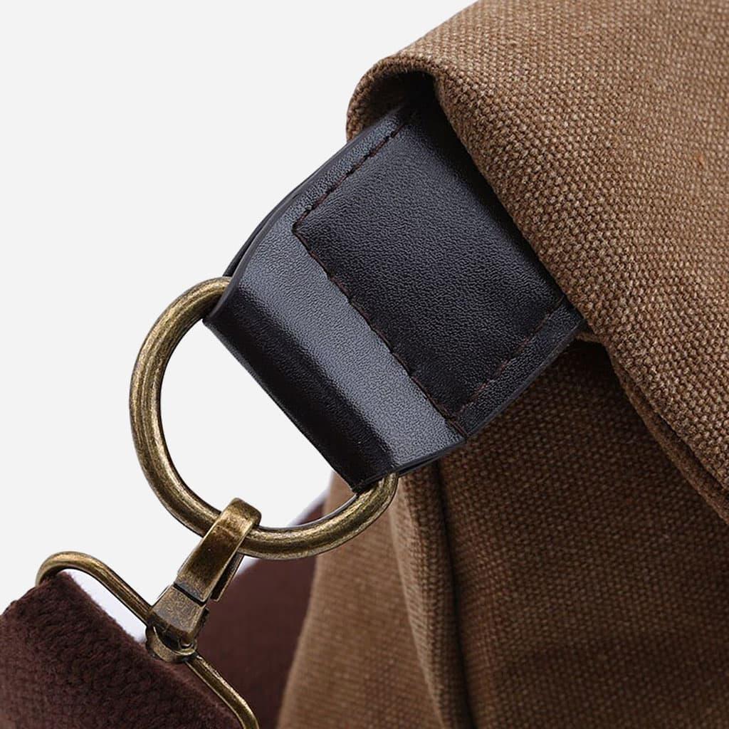 Détail de la bandoulière, de l'encoche et du mousqueton métallique couleur bronze du sac besace.