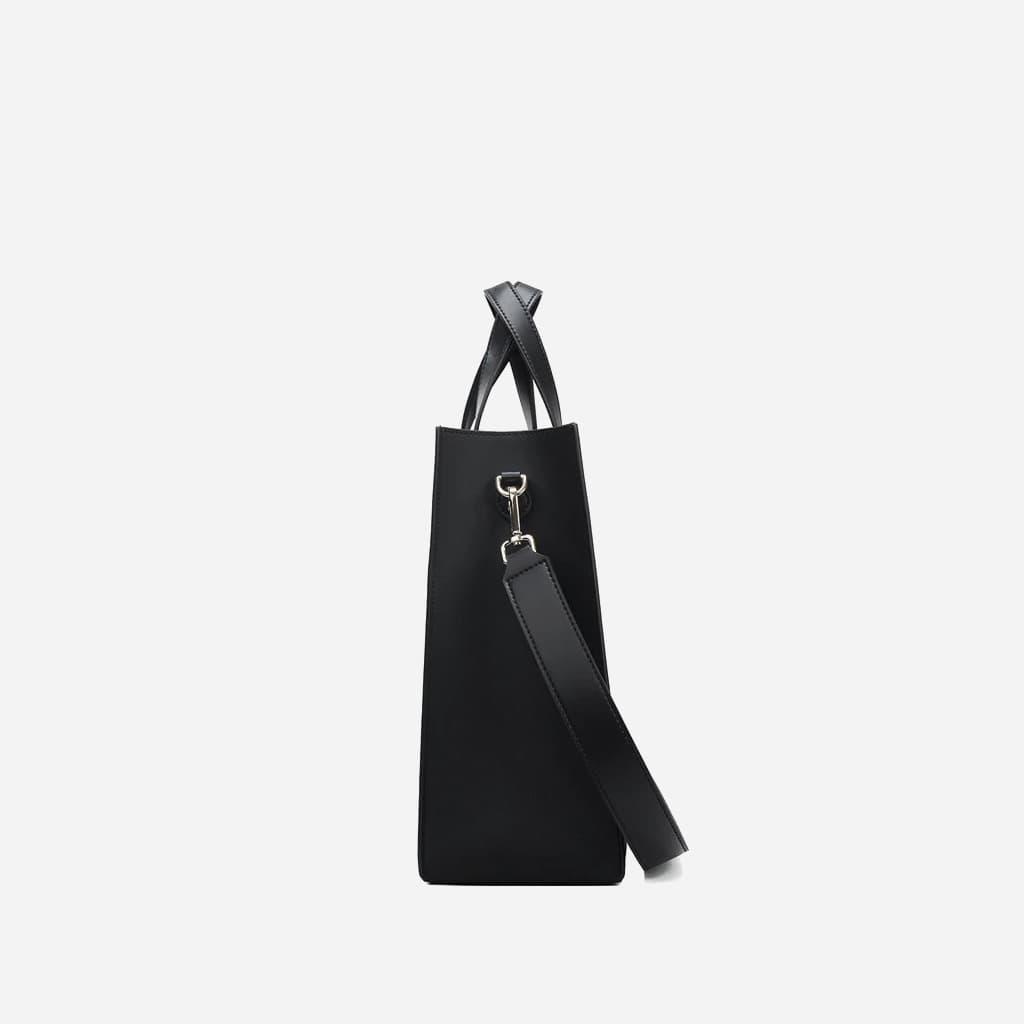Côté du sac cabas pour femme en cuir noir avec anse asymétrique et œillets