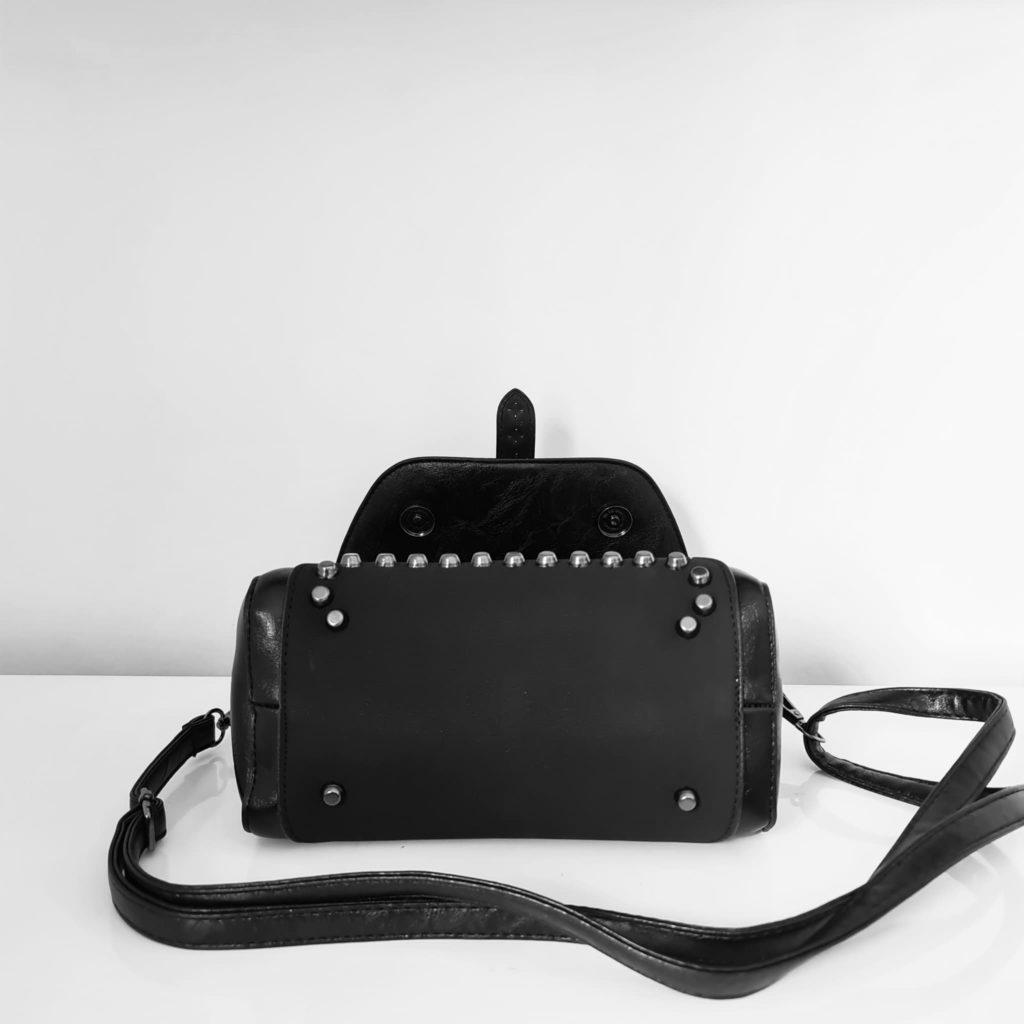 Dessous du petit sac besace en cuir noir et velours.