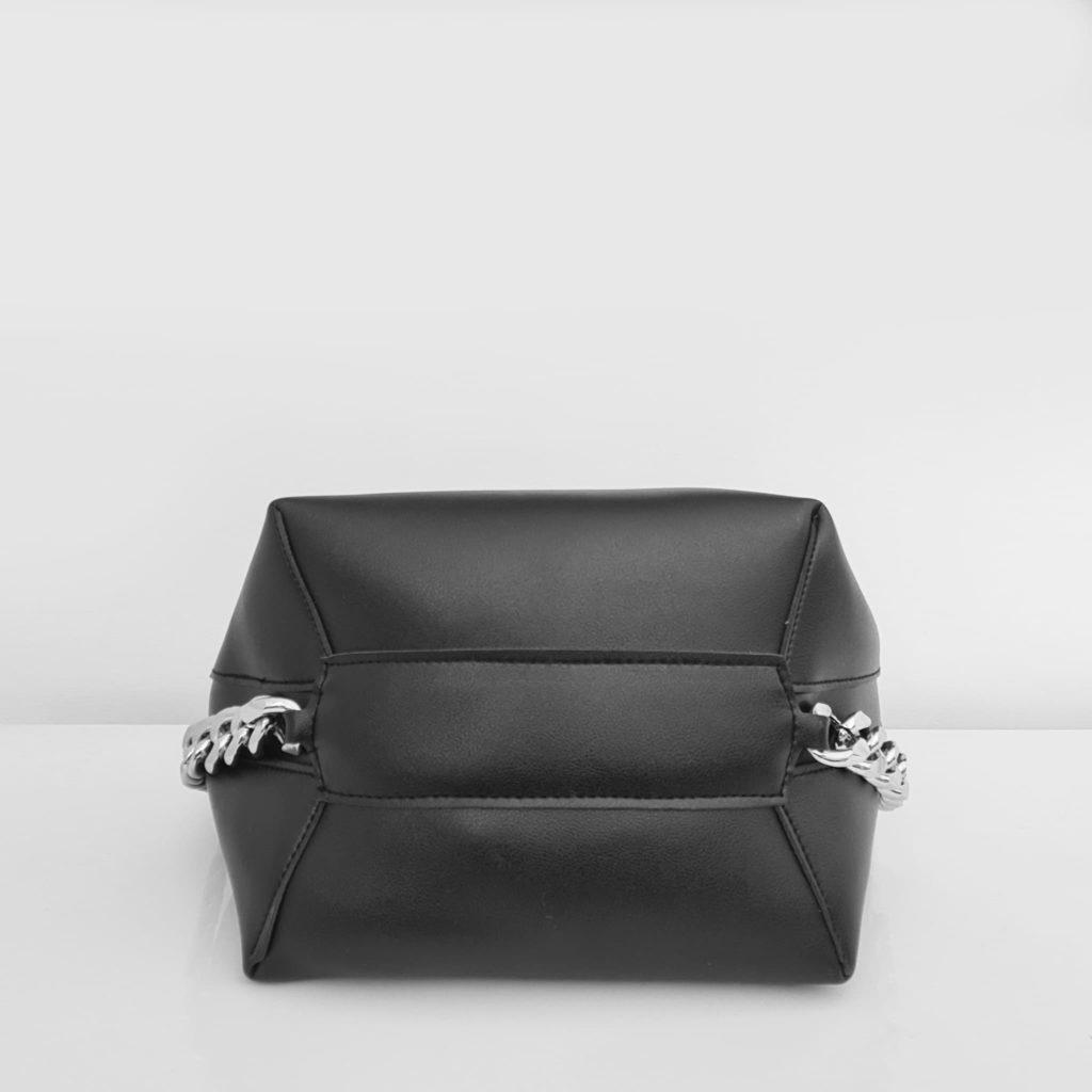 Dessous du sac seau en cuir noir avec anse bandoulière et chaîne décorative