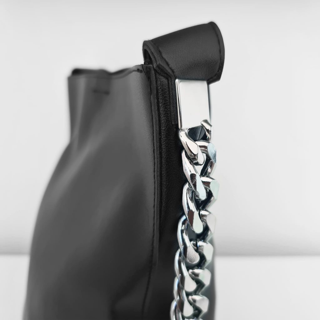 Zoom anse bandoulière et chaînes avec maillons du côté du sac seau cabas cuir noir pour femme.