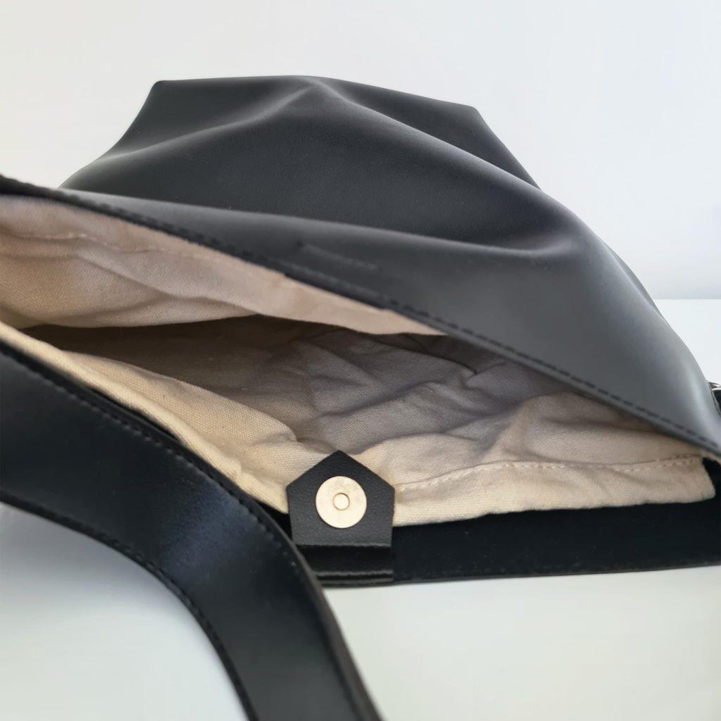 Intérieur du sac seau en cuir noir avec anse bandoulière et chaîne décorative