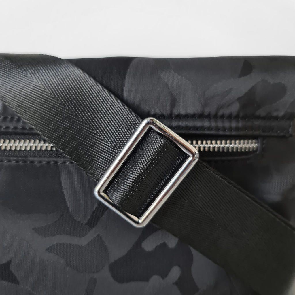 Zoom sur la bandoulière de la besace homme effet camouflage noir avec empiècement argenté.