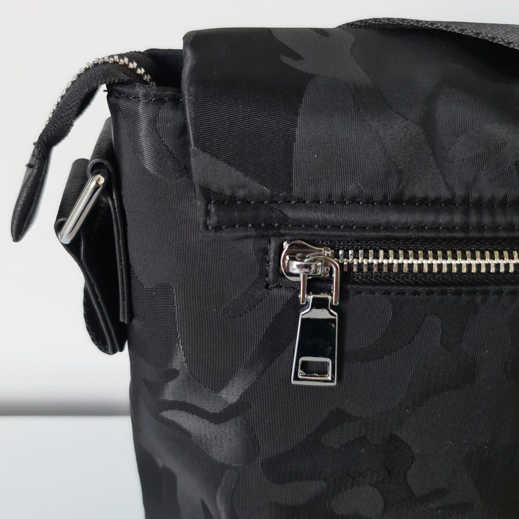 Zoom tissu camo et poche arrière du sac besace camo homme avec curseur et tirette en métal argenté.