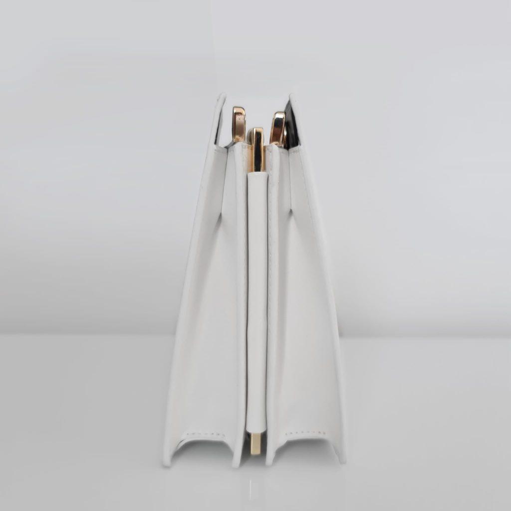 Côté du sac à main cuir blanc femme asymétrique avec anse métallique dorée
