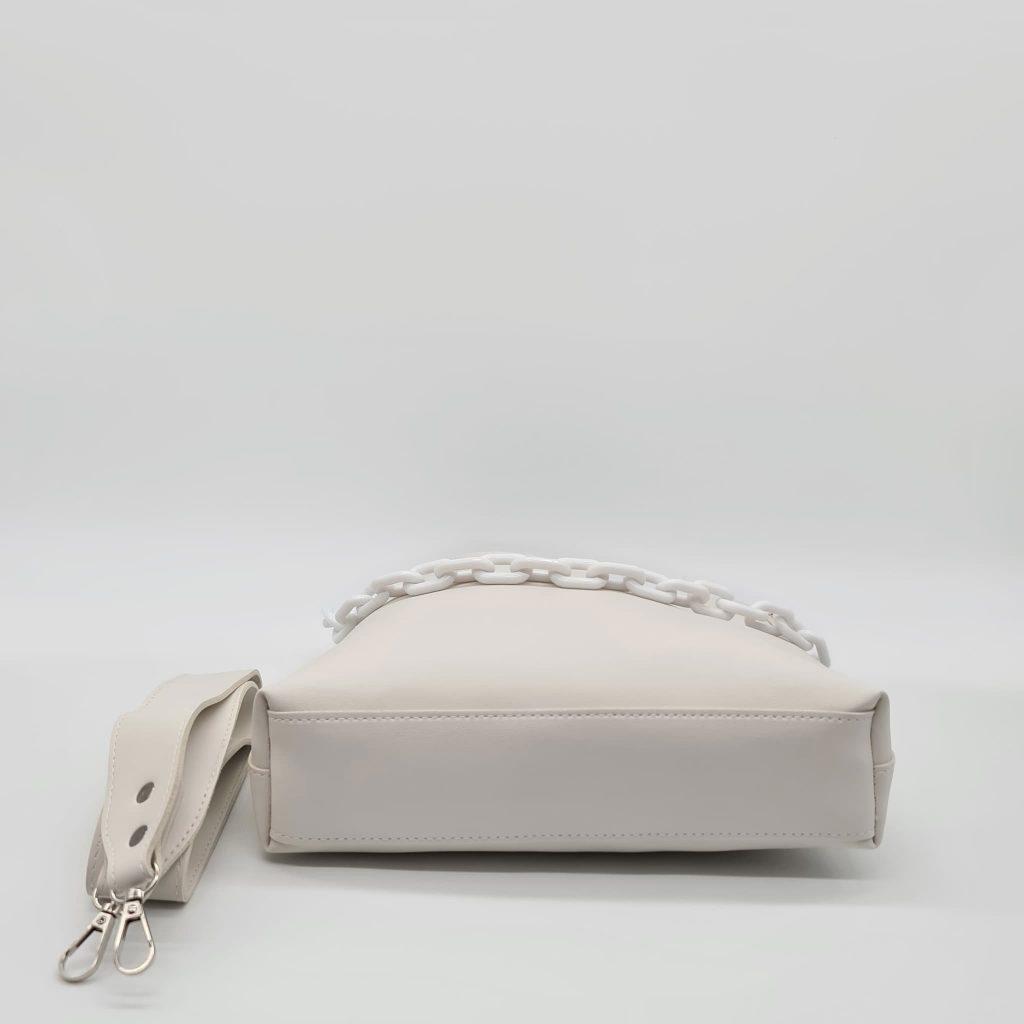 Dessus du sac à main bandoulière en cuir blanc avec sa large bandoulière noire.