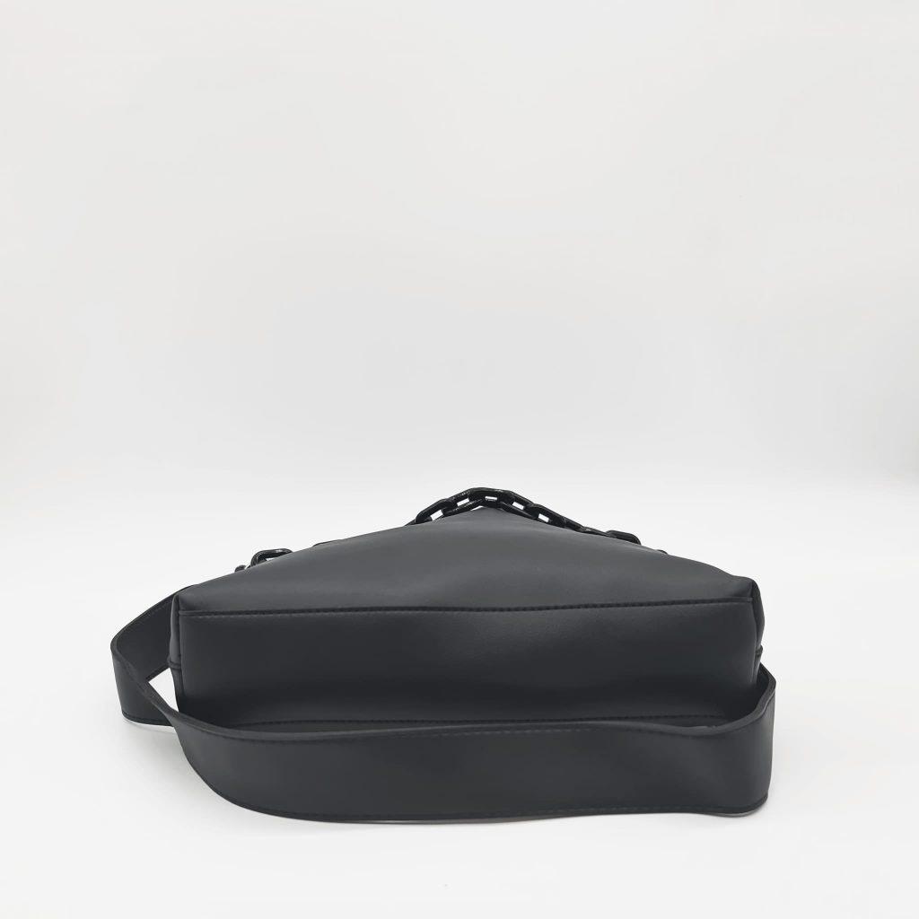 Dessous du sac à main bandoulière en cuir noir avec sa large bandoulière noire.