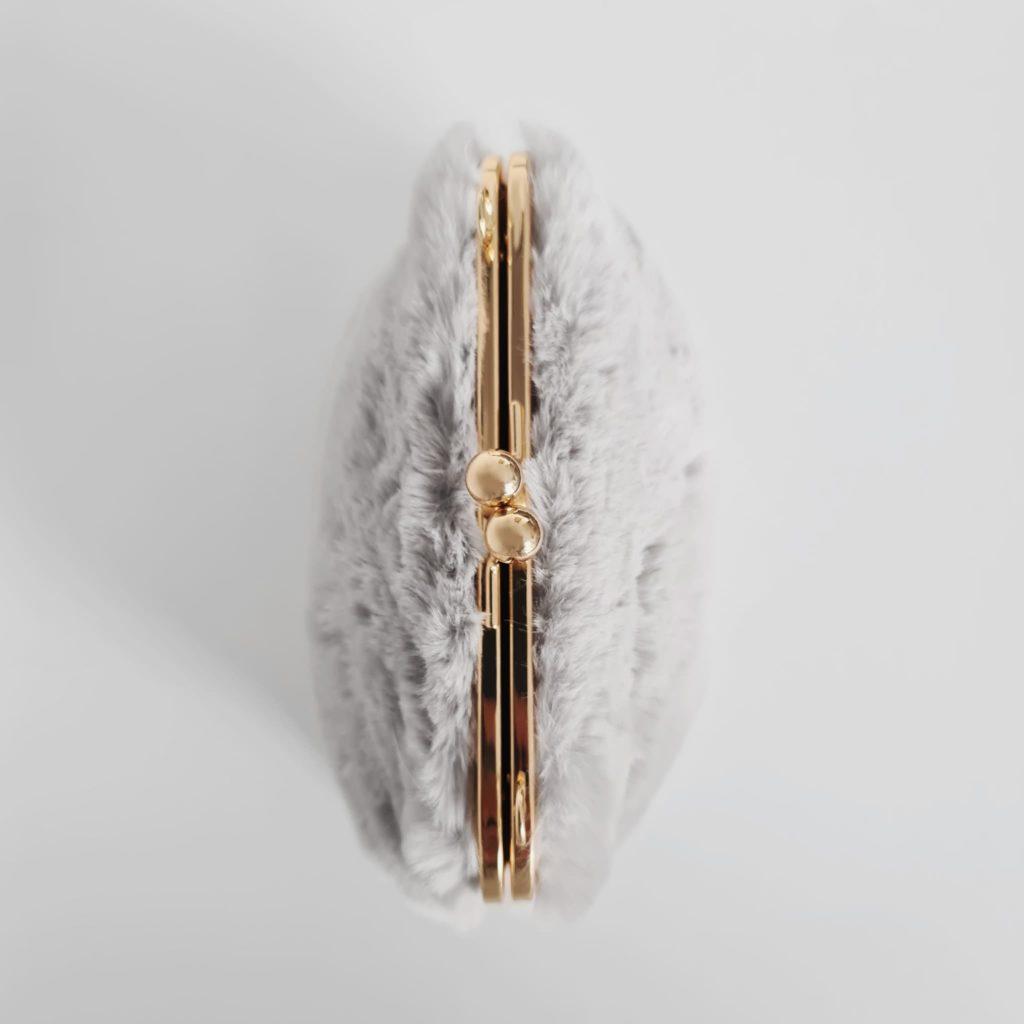 Dessus du petit sac fourrure gris clair à boucle clic clac et bandoulière à chaîne dorée