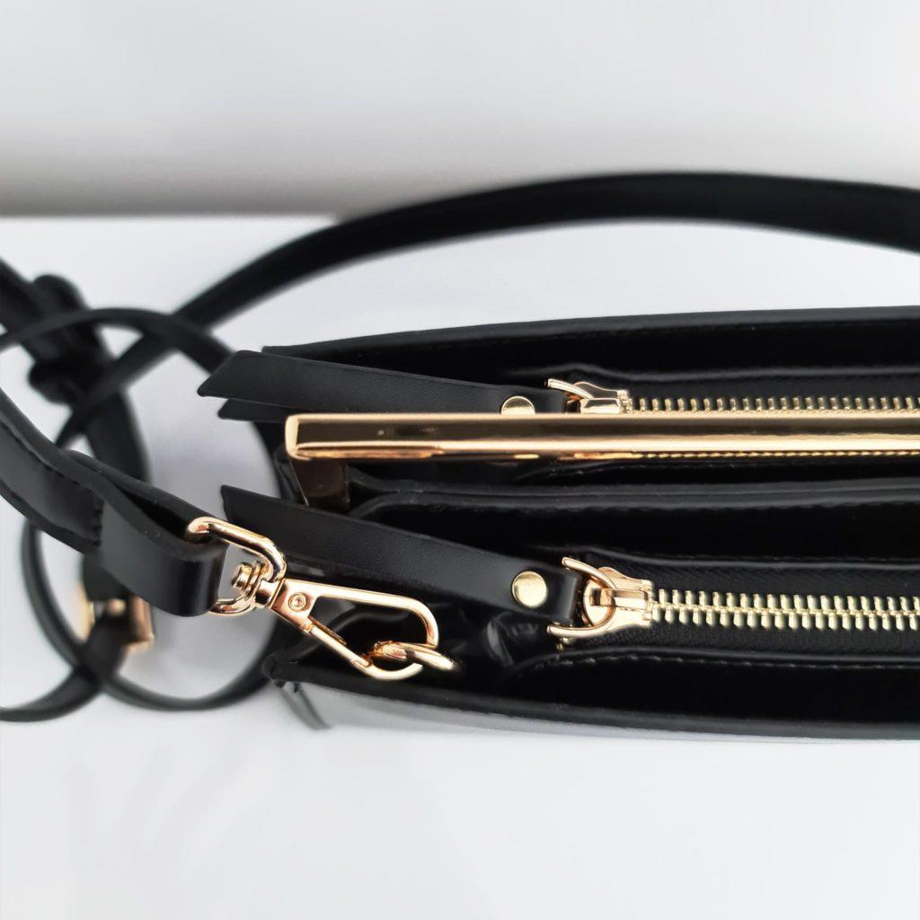 Détails du cuir noir, de la bandouilière avec mousqueton, des tirettes cuir noir et des curseurs avec fermetures à zip dorées.