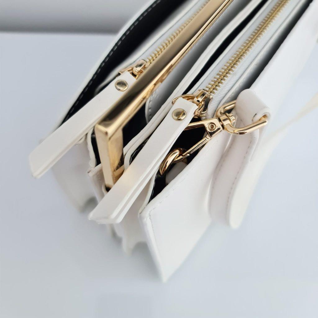 Haut du sac à main cuir blanc femme avec anse, curseurs et empiècements dorés.