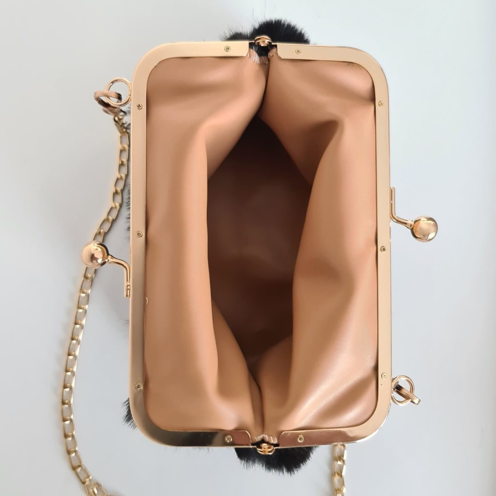 Ouverture du sac femme à fourrure noir à boucle clic clac et bandoulière à chaîne dorée