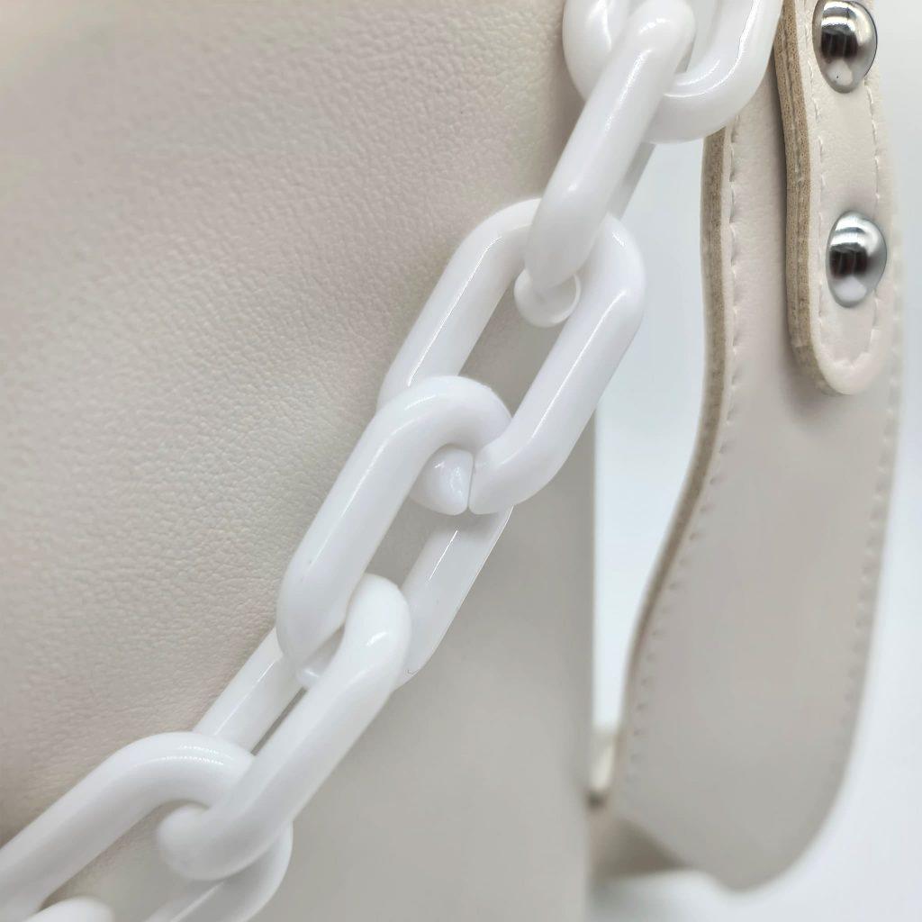 Zoom sur la bandoulière en cuir blanc et l'anse à chaîne grosse maille blanche.