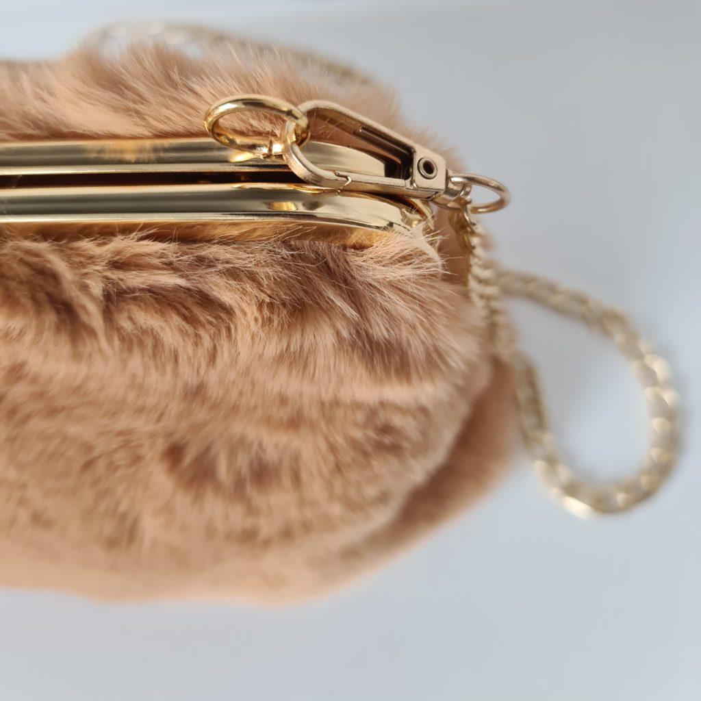 Zoom sur la fourrure camel et l'empiècement métallique doré : boucle clic clac, mousqueton, bandoulière à chaîne