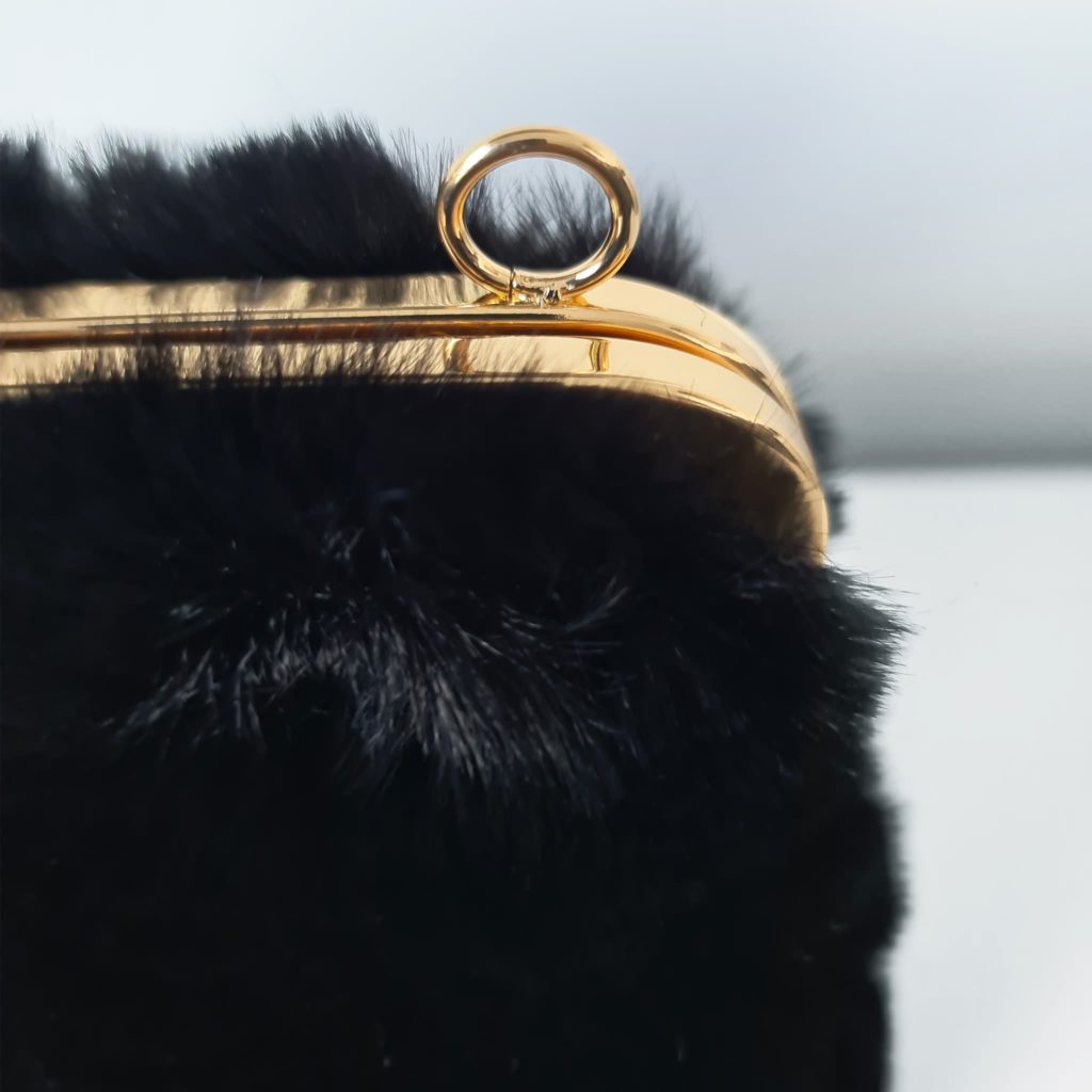 Détail fourrure noir, fermeture clic clac or doré et encoche pour bandoulière