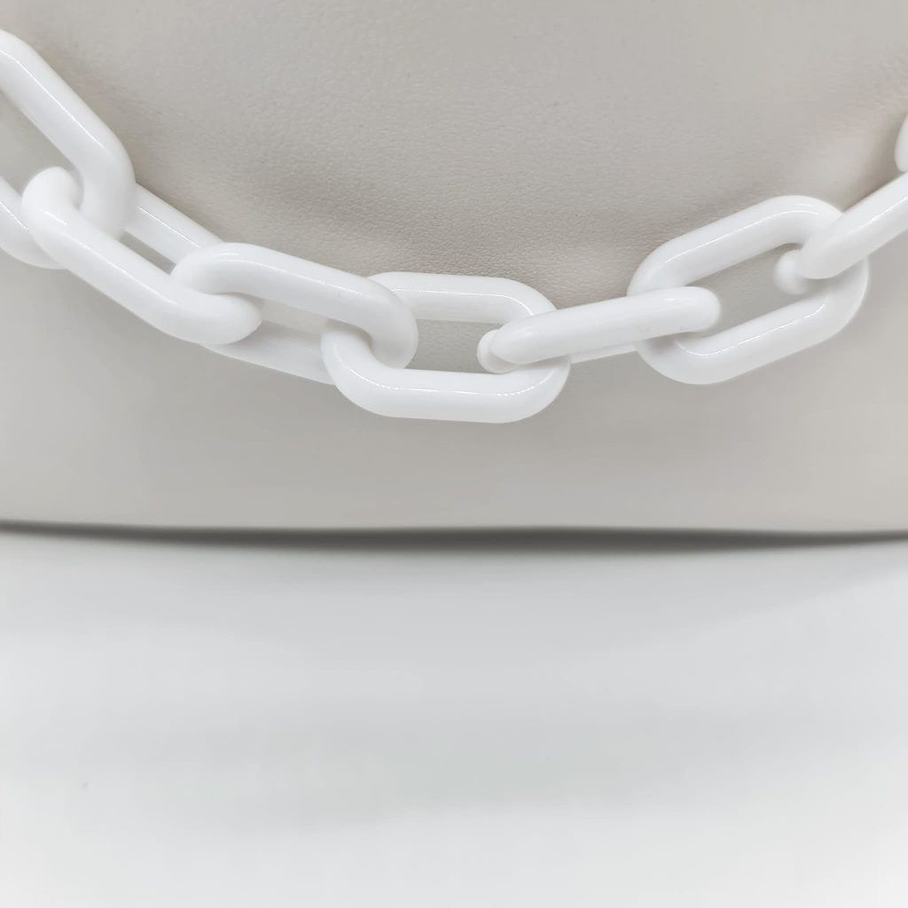 Zoom sur les maillons des chaînes de l'anse du sac à main cuir blanc femme.