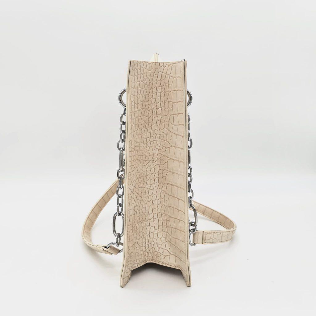 Côté (side) du sac cabas à main femme en cuir croco blanc cassé crème avec bandoulière à chaîne et cuir.