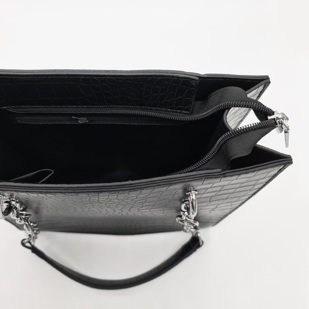 Intérieur du sac cabas à main femme en cuir croco noir avec bandoulière à chaîne et cuir.