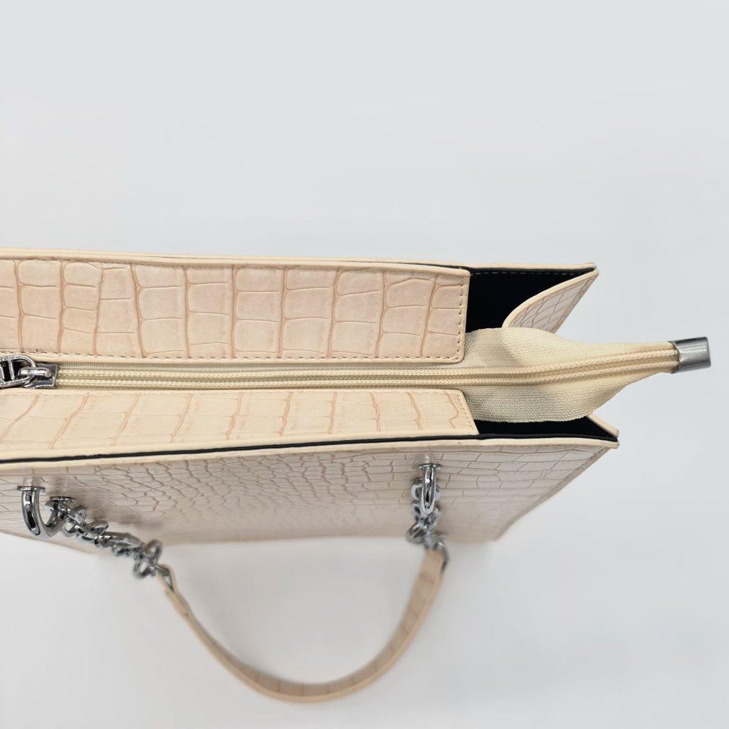 Zoom fermeture et dessus du sac cabas à main femme en cuir croco blanc cassé crème avec bandoulière à chaîne et cuir.