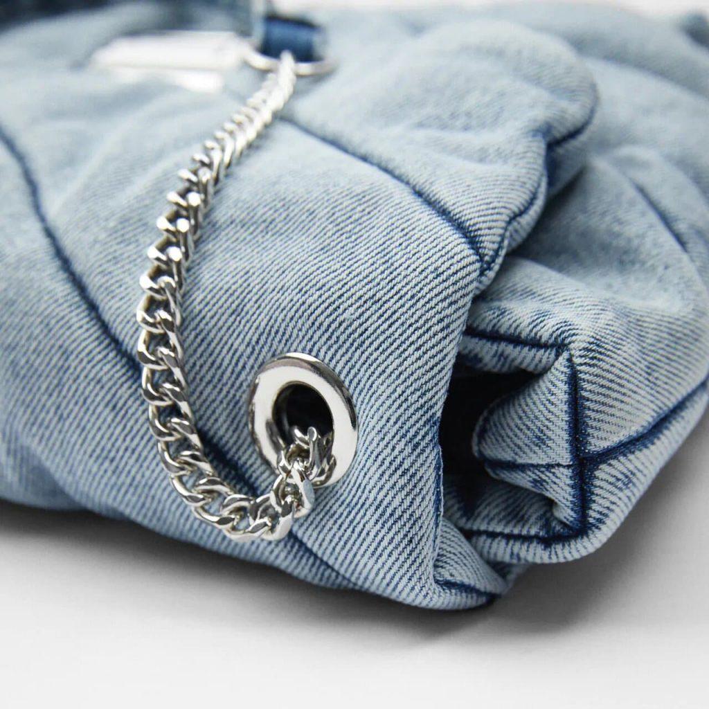 Détails du tissu en denim blue jean avec oeillet et bandoulière métallique à chaine argenté.